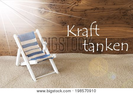 Sunny Summer Greeting Card With Sand And Aged Wooden Background. German Text Kraft Tanken Means Relax. Deck Chair For Holiday Or Vacation Feeling.