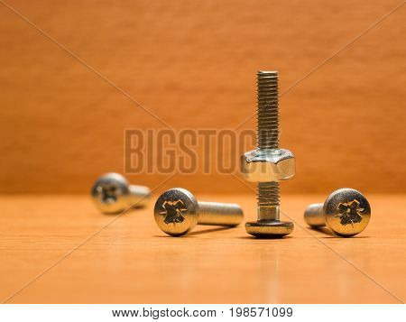 Screw upside down on which a nut is screwed on a wooden surface