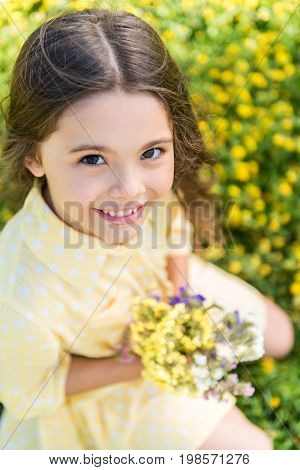 Top view of happy female child enjoying beauty of windflowers on meadow. She is sitting on grass and looking at camera with excitement. Kid is holding bouquet and laughing