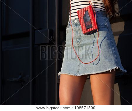 Sexy of pretty young sport style woman posing on vacation on the street having fun with vintage red cassette player. Part of body. Part of body.