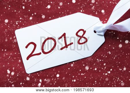 One White Label On A Red Textured Background. Tag With Ribbon And Snowflakes. English Text 2018 For Happy New Year Greetings