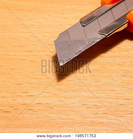 Edge of a clerical knife with an elongated blade on a wooden background such a tool is needed both in the office and in construction