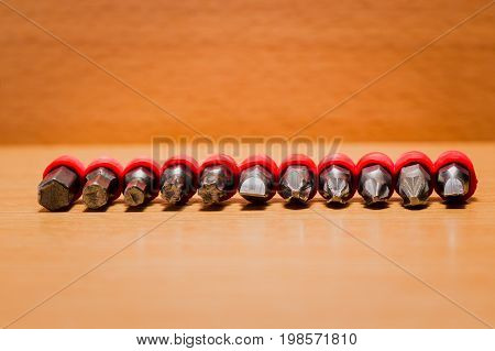 Various screwdriver bits on a wooden background small durable tools suitable for various splines