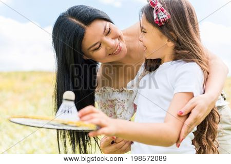 Cute little girl is learning how to throw badminton ball with the help of her mother. She is holding racket and smiling. Woman is embracing child while standing on grassland