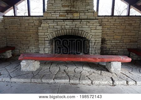 Picnickers may sit on benches beside the fireplace in the historic Shorewood Grove Shelter, in the Hammel Woods Forest Preserve in Shorewood, Illinois.