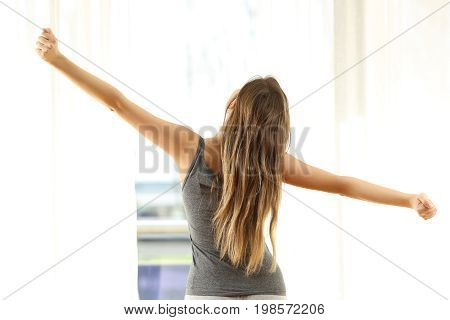 Back view of a girl stretching arms waking up looking through window in the morning at home