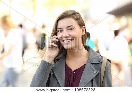 Teen smiling looking at you on the phone on the street