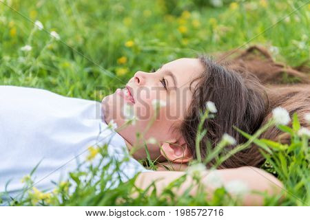 Starting new happy day. Side view of excited little girl lying on grass with relaxation. She is looking at to the sky and smiling