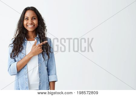 Fashionable emotional young African American female wearing denim shirt pointing her index finger at white blank wall background behind her, looking positive and happy, broadly smiling.