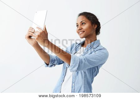 Selfie time. Joyful young attractive Afro-american woman with dark hair in blue shirt making selfie, holding tablet in her hands. Dark-skinned youn beautidul girl posing for selfie on white background.