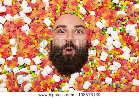 From above shot of bearded man lying in candies and looking excitedly at camera.