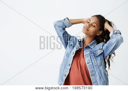 Studio shot of beautiful Afro-american girl in denim jacket with closed eyes playing with her long dark wavy hair. Young woman posing on white background.