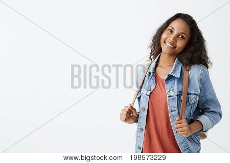Stylish Afro-American girl with dark wavy dark hair having fun indoors and looking at camera with cheerful smile. Beautiful young lady in denim jacket smiling happily keeping hands on her rucksack shoulder straps, isolated on white.