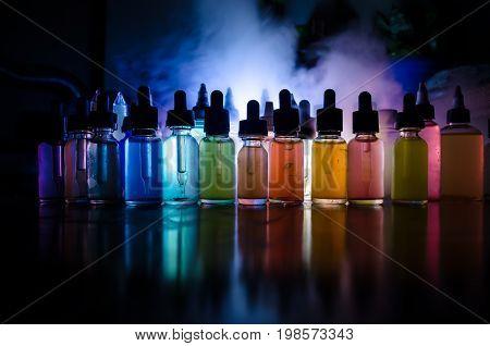 Vape Concept. Smoke Clouds And Vape Liquid Bottles On Dark Background. Light Effects. Useful As Back