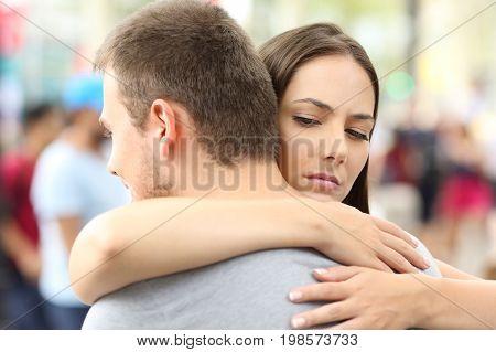Discontent girlfriend hugging her partner on the street