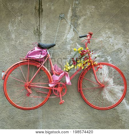 Vintage bike hanged up, used as decoration, with some flowers. Color image.