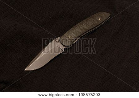 Black Knife On A Black Background. Front View. Black On Black.