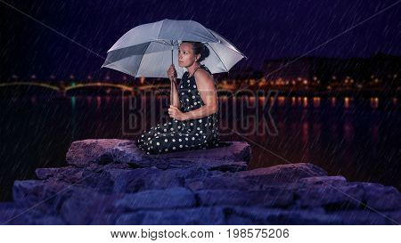 Rocky, rain kneeling female model with umbrella in hand, night background