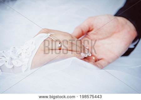 Bride and groom with wedding rings and bridal dress