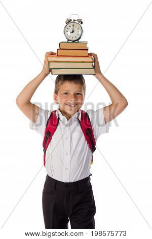 Happy funny schoolboy standing with book and alarm clock over head, isolated on white