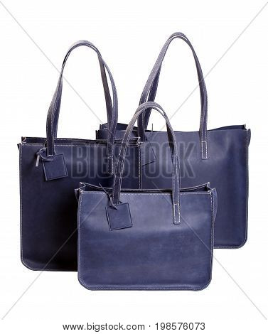 Three luxury women's handbags blue isolated on white. Macro photo.