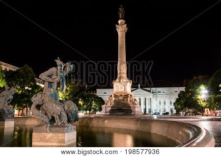 Portugal, Lisbon, Rossio Square by night with Baroque fountain and Column of Dom Pedro IV