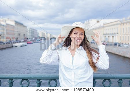 A beautiful and smiling girl in a white hat with wide brim is standing on the bridge and talking on the phone against the background of blue storm clouds.