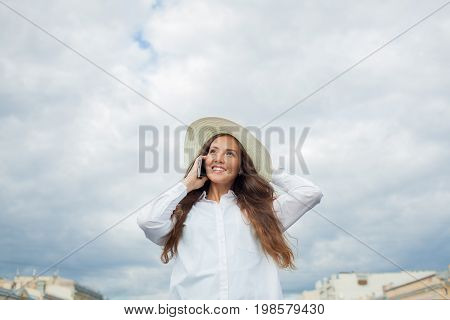 A Beautiful And Smiling Girl In A White Hat With Wide Brim Is Standing On The Bridge And Talking On