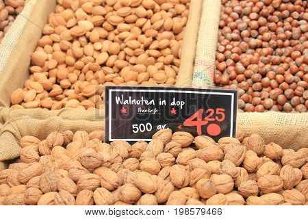 Fresh unpealed nuts on a market stall (text on tags: names and prices of various nuts in Dutch walnuts Pecan almonds and hazel)