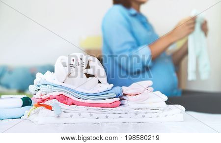 Pile Of Baby Clothes, Stuff And Pregnant Woman In Home Interior