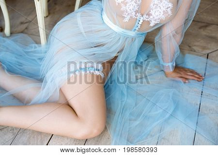Beautiful sexy lady in elegant blue robe and garter. Close up female fashion portrait of model indoors. Beauty woman with attractive body in lace lingerie. Closeup naked girl in underwear