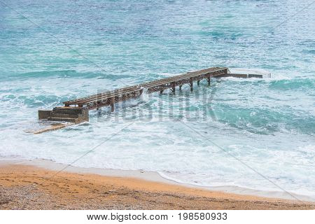 Rusty sea pier. Rusty isolated lonely pier on the background of the sea, waves crashing into the pier