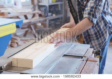 Young carpenter working with circular saw in shop, closeup