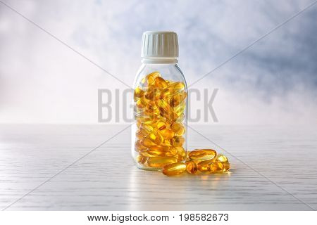 Bottle with fish oil capsules on light background