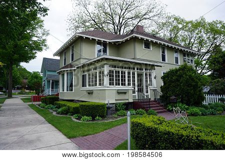 CADILLAC, MICHIGAN / UNITED STATES -  MAY 31, 2017: An elegant stucco home, with an enclosed front porch, in Cadillac's Courthouse Hill Historic District.