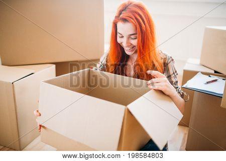 Woman unpacking cardboard boxes in new home
