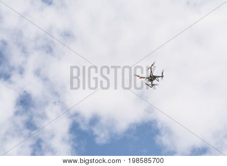 Hovering drone taking pictures a clouds on front