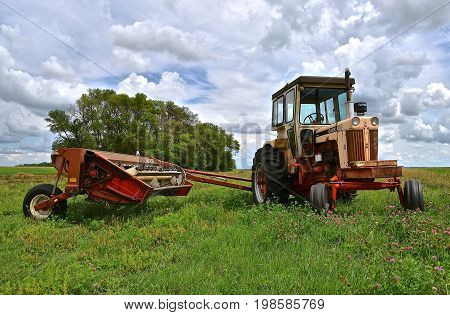 PELICAN RAPIDS, MINNESOTA, August 5, 2017: The old 930 Case tractor pulling a hay conditioner  is from the Case Corporation which was a manufacturer of construction equipment and agricultural equipment, founded by Jerome I. Case, it existed for over 150 y
