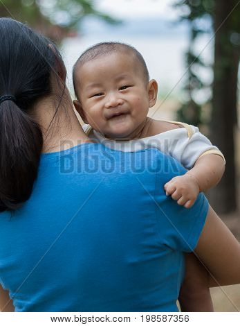 Asian baby feeling happy with his mom
