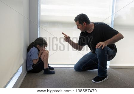 Angry father (age 40-45) angry with his bad daughter (age 07) sitting in the corner on the floor. Family life concept. Real people. Copy space