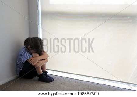 Sad child girl (age 07) sits in the corner. Childhood sadness concept. Real people. Copy space
