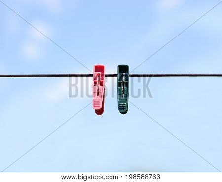 Green And Red Clothespins On The Rope. On The Background Of Blue Sky. Closeup