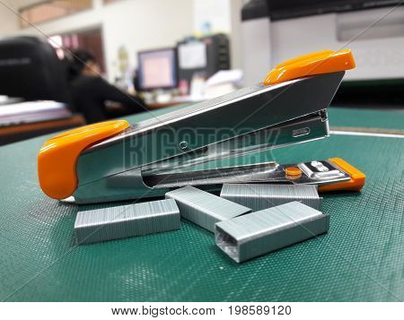 Stapler and staples on table with blurred office background.