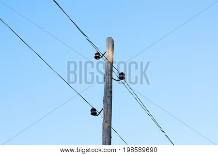 A Wooden Post With Wires Electricity. On The Background Of Blue Sky