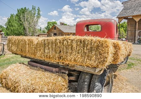 Old flatbed truck with a red cab loaded with fresh hay