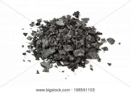 Heap of black flakes on white background