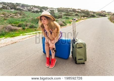 Sad woman sitting on suitcase. Stressed young tourist woman sitting on suitcases