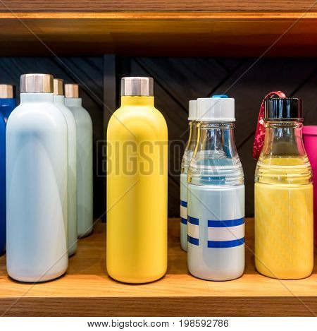 Stainless steel vacuum water bottle with twist off lid for cold beverages on wooden shelf. Easy carry design for travel or sports.
