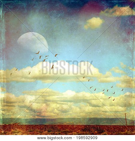Rural surreal landscape with flat road and power lines in foreground and mountain range in background under a cloud filled blue sky with moon and flock of birds. Vintage grunge textured image with copy space.