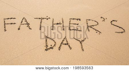 Father's Day hand written in the sandy beach.